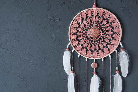 bedroom design: Pink ash crochet doily dream catcher close up on dark gray textured background. Texture of concrete, copy space for text Stock Photo