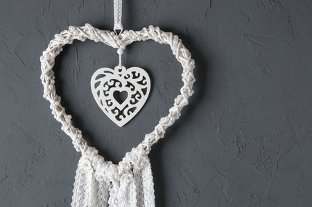 White heart lace dream catcher close up  on dark gray textured background. Texture of concrete,copy space for text