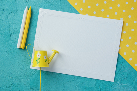 Yellow white polka dot texture, blank note and wax pencils on aquamarine textured background.Top view and copy space for text