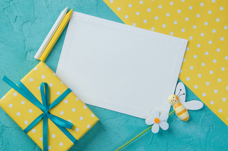 Yellow white polka dot texture, blank note, wax pencils and gift box with a bow on aquamarine textured background.Top view and copy space for text Stock Photo