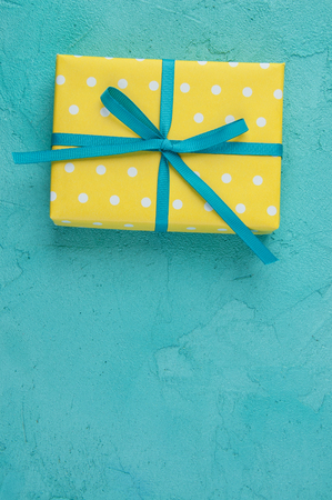 Yellow white polka dot gift box with a bow on aquamarine textured background.Texture of concrete and copy space for text