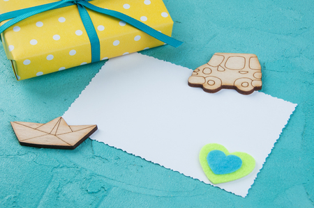 Yellow white polka dot gift box with a bow , wooden car and boat, felt heart and white blank on aquamarine textured background.Texture of concrete and copy space for text Stock Photo