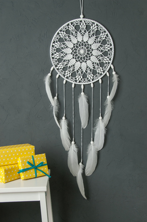White dream catcher , white bedside table  and yellow white polka dot boxes in bedroom interior on gray textured background. Bedroom decor Stock Photo