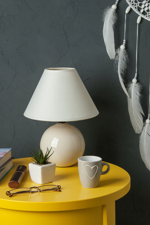 White dream catcher ,yellow bedside table , plant, mug and lamp in bedroom interior on dark gray textured background. Bedroom decor
