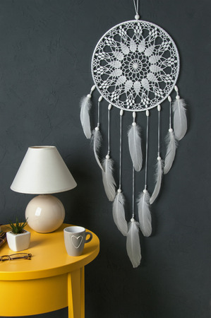 White dream catcher ,yellow bedside table , plant, mug and lamp in bedroom interior on dark gray textured background. Texture of concrete