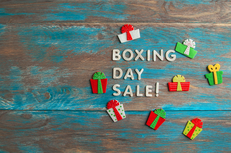 Boxing day sale and felt gift boxes on blue shabby wooden background