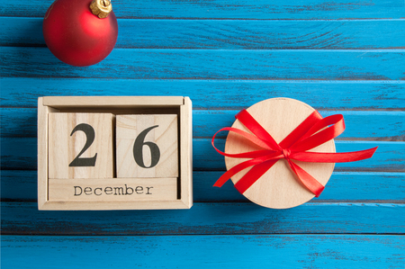 Boxing day sale , wooden calendar and gift box with red bow on blue shabby wooden background