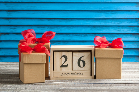 boxing day: Boxing day sale , wooden calendar and gift boxes with red bows on blue shabby wooden background