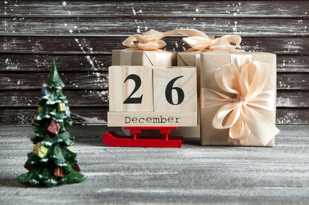 generosa: Boxing day sale , wooden calendar and gift boxes with bows on brown shabby wooden background Foto de archivo
