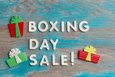 tradition: Boxing day sale and felt gift boxes on blue shabby wooden background