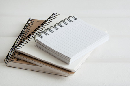 white sheet: Notebooks on white wooden background.Copy space for text.