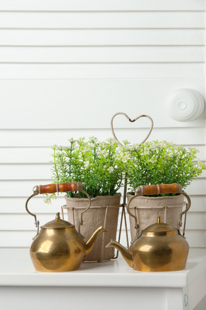 Brass teapots on white door background Stock Photo