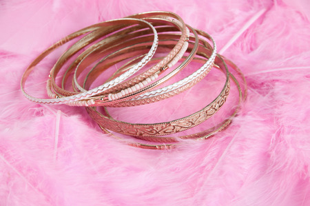 Many bracelets on pink fearhers textured background