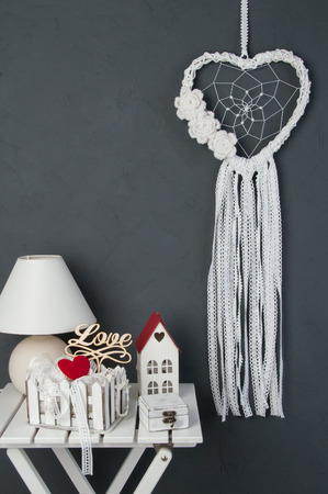 White heart lace dream catcher with crochet flowers, white nightstand , shabby wooden casket , candlestick. red heart and shabby basket with lace  on dark gray textured background. Texture of concrete,copy space for text