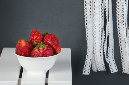 White bowl of strawberry, white nightstand on dark gray textured background. Texture of concrete,copy space for text