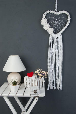 White heart lace dream catcher with crochet flowers, white nightstand , shabby wooden casket , plant,red heart and shabby basket with lace  on dark gray textured background. Texture of concrete,copy space for text