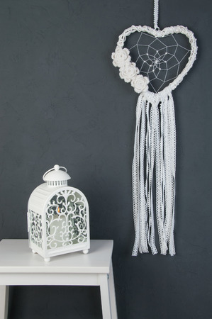talisman: El colector ideal del cordón del corazón blanco con el ganchillo florece, el nightstand blanco y la palmatoria en fondo texturizado gris oscuro. Textura de hormigón, copia espacio para texto