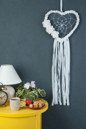 White heart lace dream catcher on dark gray textured background. Bedroom decor, copy space for text.