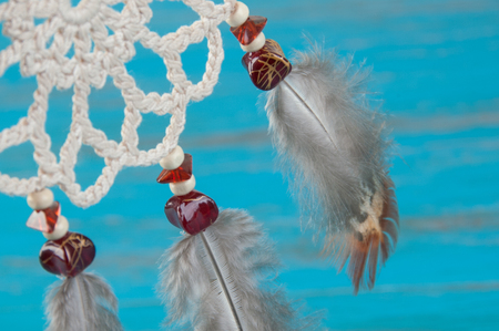 Mini beige dream catcher close up on blue background. Stock Photo