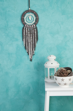 Beige Brown dream catcher , white bedside table , candlestick and bowls with rattan balls in bedroom interior on aquamarine textured background. Bedroom decor.