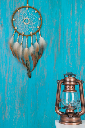 talisman: Olive dream catcher , white bedside table and candlestick on wooden shabby blue background. Copy space for text Foto de archivo