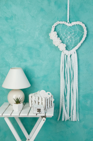 White heart lace dream catcher with crochet flowers, white bedside table and shabby decor on aquamarine textured background. Texture of concrete, copy spzce for text. Stock Photo