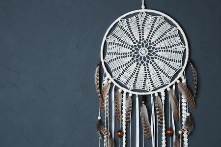 クリーム色のかぎ針編みドイリー ドリーム キャッチャーすぐを灰色のテクスチャ背景。コンクリート、コピーのテキストのための領域のテクスチャ