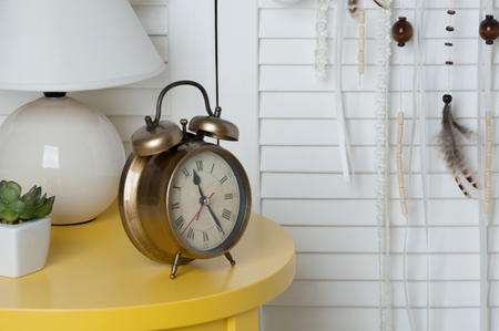 Cream crochet doily dream catcher , yellow nightstand and alarm clock on door background. Copy space for text Stock Photo