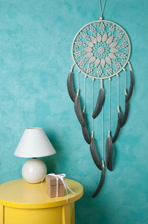 Beige crochet doily dream catcher , yelioow nightstand , table lamp and gift box on aquamarine textured background. Texture of concrete,copy space for text