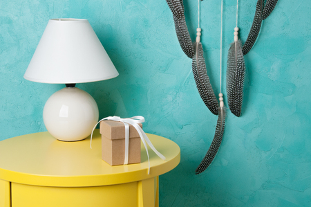 Gift box with bow and lamp in bedroom interior on aquamarine textured background. Bedroom decor Stock Photo