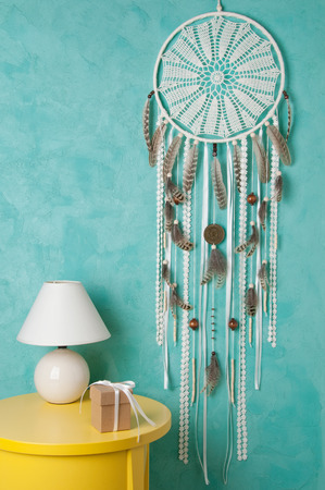 Cream crochet doily dream catcher , yelioow nightstand , table lamp and gift box on aquamarine textured background. Texture of concrete,copy space for text