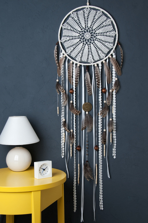 Cream crochet doily dream catcher, yelioow nightstand , table lamp and alarm clock on gray textured background. Texture of concrete,copy space for text