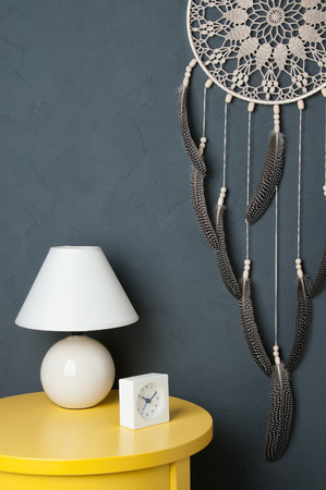 Beige crochet doily dream catcher ,yelioow nightstand , table lamp and alarm clock on dark gray textured background.