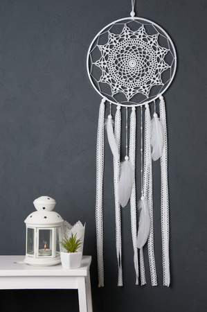 White crochet doily dream catcher , white nightstand and candlestick on gray textured background. Texture of concrete,copy space for text