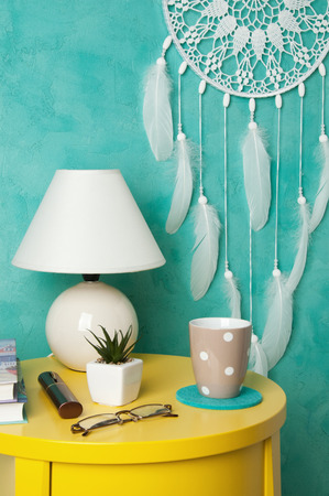 White crochet doily dream catcher , yelioow nightstand , table lamp and cup on aquamarine textured background. Texture of concrete,copy space for text