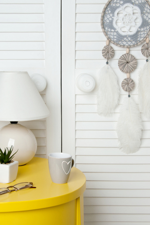 Gray white crochet doily dream catcher , yelioow nightstand , table lamp and cup on door background. Copy space for text