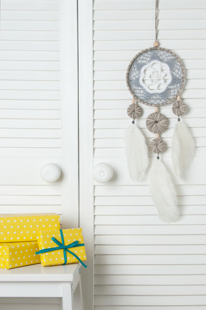 Gray white crochet doily dream catcher , white bedside table and yellow white polka dot boxes in bedroom interior on  door background.