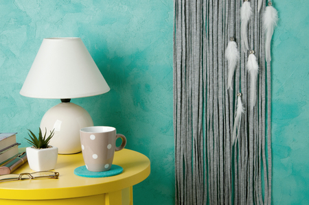 Gray white dream catcher , yellow nightstand and white lamp on aquamarine textured background. Copy space for text Stock Photo