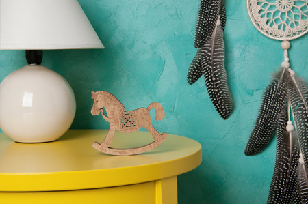 White table lamp and wooden toy horse in bedroom interior on aquamarine textured  background. Bedroom decor. Stock Photo
