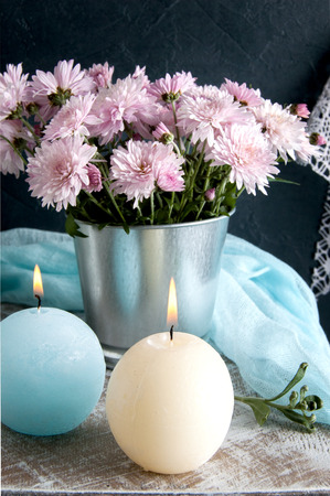 textured wall: Blue and cream aroma candles and rose chrysanthemums. Bedroom decor.
