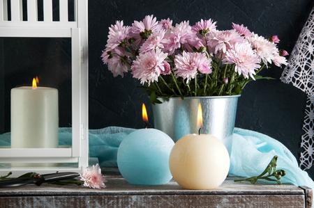 青とクリームの香りのキャンドルとバラ菊。寝室の装飾。