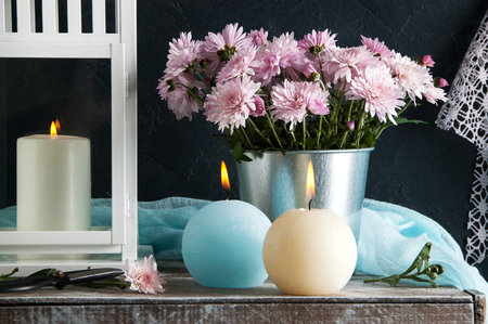 Blue and cream aroma candles and rose chrysanthemums. Bedroom decor.