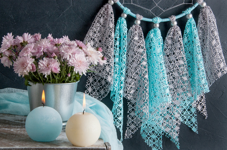 Gray blue lace dream catcher, flowers and candles in bedroom interior on black textured background. Bedroom decor Stock Photo