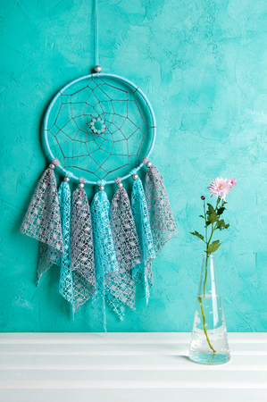 Gray blue lace dream catcher and rose chrysanthemums on aquamarine textured background. Copy space for text.