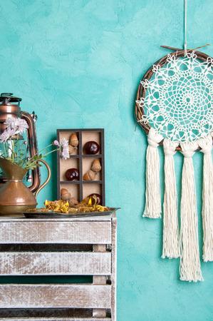 Cream crochet doily dream catcher , shabby nightstand  and aroma candles on aquamarine textured background. Bedroom decor. Foto de archivo