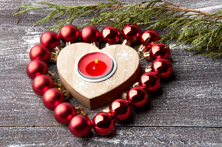 Wooden Christmas heart candlestick with red candle and red balls on shabby wooden brown background. Christmas decorations, copy space for text.