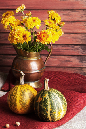 Pumpkins,copper jug with yellow chrysanthemums. Holiday decorations, copy space for text. Stock Photo