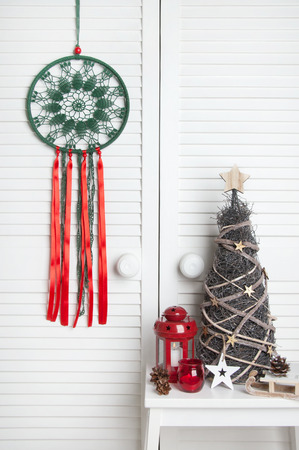 Green red crochet doily dream catcher , red candlestick and wooden christmas tree on white door background. Christmas decoration and copy space for text