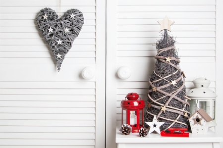 Wooden christmas tree and heart, red and white candlesticks on white door background. Christmas decoration and copy space for text