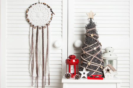 White brown crochet doily dream catcher , red and white candlestick and wooden christmas tree on white door background. Christmas decoration and copy space for text Stock Photo
